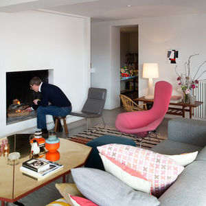 living room with concrete floors, white walls, gray Cappelini sofa, and pink Harry Bertoia wire chairs