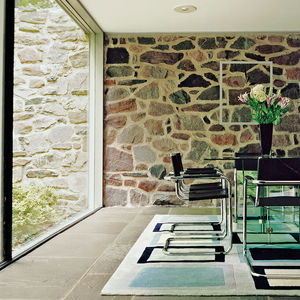 Renovated Breuer house interior with glass and stone walls and tubular steel dining chairs
