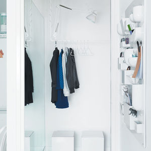 an open closet with a mirror and suspended lamp in the foyer of an apartment