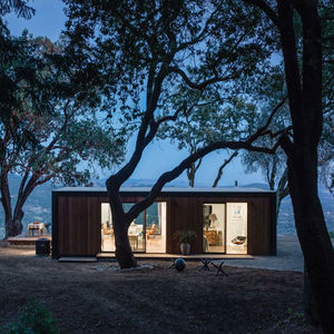 Modern prefab home at night with tall trees