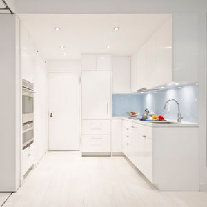 modern kitchen renovation with white cabinets and glass backsplash