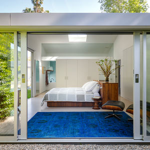 Floor to ceiling sliding glass doors in the master bedroom of a Bel Air ranch-style home