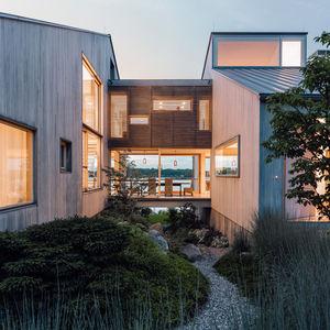 new head of its class connecticut renovation summer home facade bleached cedar siding volumes glass bridge