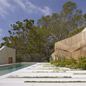 Undulating wooden wall and white cast stone pavers from Napa Valley Cast Stone in Los Angeles pool and patio.