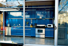 The minimal aesthetic is seen in the galley-style kitchen, where the cabinets have no visible hinges or knobs. The stainless steel  appliances are by KitchenAid.
