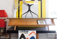 Vintage white chair, Calder print, and wood table