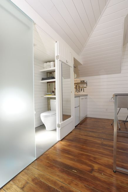 The bathroom in this converted 360-square-foot carriage house in San Francisco, the architect shoehorned a small bathroom next to the kitchen, under the dormer. The etched translucent glass lets light into the main living area and serves as one side of the shower. Photo by Susanne Friedrich.