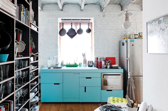 "http://www.dwell.com/house-tours/slideshow/true-value The centerpiece of Lukáš Kordík's new kitchen is the cabinetry surrounding the sink, a feat he managed by altering the facing and pulls of an off-the-rack Ikea system. The laminate offers a good punch of blue, and in modernist fashion, Kordík forwent door handles in favor of cutouts. ""I wanted the kitchen to be one simple block of color without any additional design,"" he says."