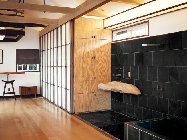 Custom shoji-inspired screens of Roberts's design conceal the closet and extend to provide privacy for the adjacent shower and soaking tub.   Photo by Joe Pugliese.