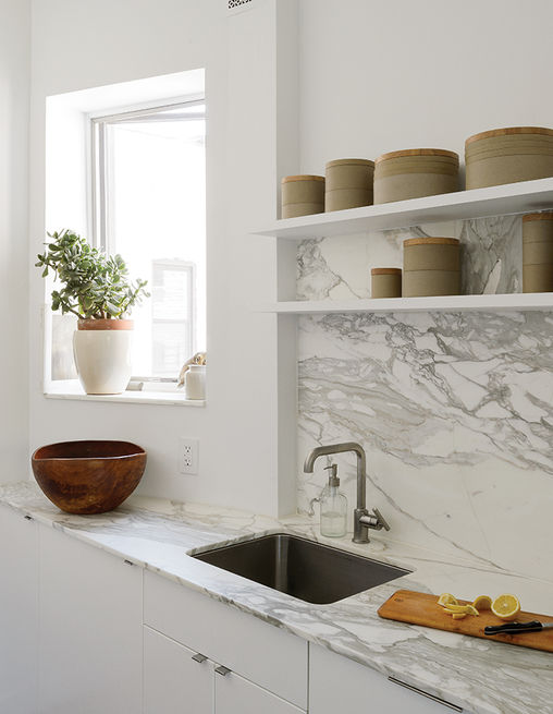 The showstopping material elements are the Borghini honed marble countertop and backsplash by Ann Sacks. Hasami porcelain vessels line the open shelving.  Photo by: Matthew Williams