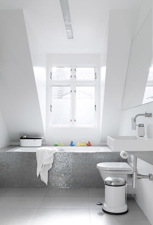 Sofie and Frank built a box around an ordinary glass fiber shell bathtub, then covered it in a mosaic of shower tiles. Natural light from a large dormer window gives the tiles an almost iridescent glow. The toilet is Duravit.   Courtesy of Vipp.
