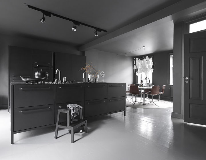 """The kitchen is the room we use the most,"" Sofie says. The dark gray walls and tonal accents make it cozy and cave-like, while natural illumination and light-toned accessories introduce airiness and circulation. Even in the colder months, the Egelunds spend most of their time there, and Sofie maintains that the stark darkness makes it a homey place to entertain guests and spend time with the family. ""And,"" she adds, ""you can always go to the other floors if it gets too dark!"" The kitchen island, shelves, glass, and ceramics are by Vipp.   Courtesy of Vipp."