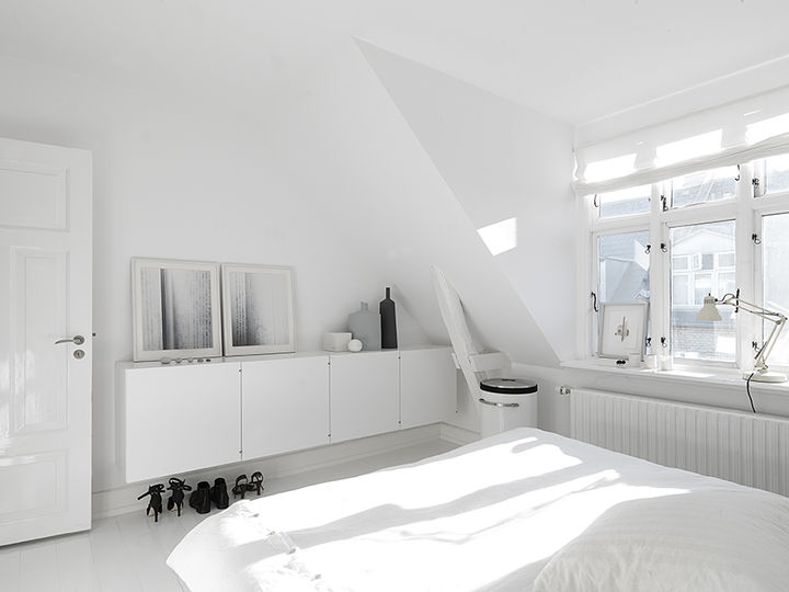 On the upper floors, bright white walls and plenty of natural light make the bedrooms and living rooms feel large and spacious. In the master bedroom, built-in cabinetry hides clutter. The art photography against the wall is by Anders Hviid, the bed is Hästens, the laundry basket is Vipp, and the lamp is Fontana Arte.    Courtesy of Vipp.