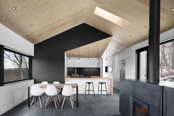 "<br /><br /><br /><br />  The architects stuck to a gray-scale color palette, installing slate tile floors that softly contrast with the white walls and Eames dining chairs. ""It lets the views out the windows become the focus,"" Dworkind explains. Doses of pure black accent important features, like the central wall that divides the kitchen and master bedroom behind it from the main living space.  Photo by Adrien Williams.<br /><br /><br /><br />"