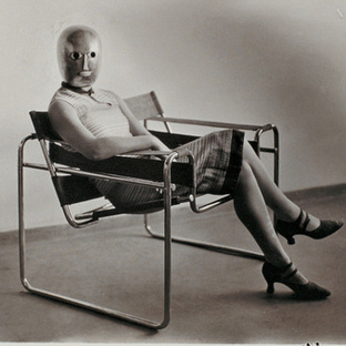 Untitled (Woman [Lis Beyer or Ise Gropius] in B3 club chair by Marcel Breuer wearing a mask by Oskar Schlemmer and a dress in fabric designed by Beyer).