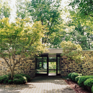 Massive fieldstone walls frame a glass entrance foyer, which allows tantalizing views through the center of the house. Built for a wealthy Baltimore couple in a forest with views of a lake, the house is a rural retreat but only a short drive to the center