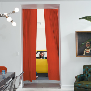 At the edge of the dining room, with its eclectic collection of fixtures and furnishings, orange velvet curtains playfully frame an opening to the skylight garage. It serves as a kind of sculpture gallery for motorcycles and cars, including one of Surratt