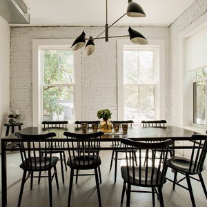 Modern dining area with black furniture and David Weeks pendant light