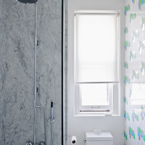 """In the bathroom, the gray Carrara walls are offset by bright tulip-patterned wallpaper, circa 1970, from Secondhand Rose in Tribeca. The toilet is a Philippe Starck """"jet action"""" model from Duravit."""