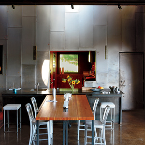 """A custom recycled-Douglas fir table by VanEyk Custom Woodworks is the heart of the living-dining room in the so-called """"Scrap House."""" The double-height wall is clad in the same steel that wraps the exterior. <a href=""""http://www.dwell.com/articles/scrap-ho"""