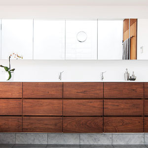 Dark walnut cabinets with Corian counter in a Toronto bathroom