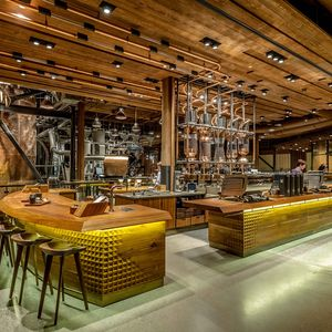 Starbucks Roastery in Seattle with wood stools and bar and roasting machines