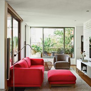 São Paulo apartment living room with red Muuto sofa, Moroso armchair, and Vitra storage unit