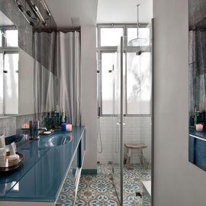 Tel Aviv bathroom with tiled floor and blue glass cabinet