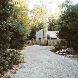 Modern small space Rhode Island cottage facade with Alaskan yellow cedar cladding and red cedar fencing