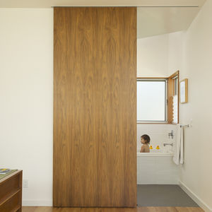 Bathroom with tub closed off by custom walnut door