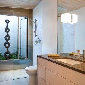 Leucos light fixture and Birgit Piskor sculpture in bathroom of British Columbia cabin
