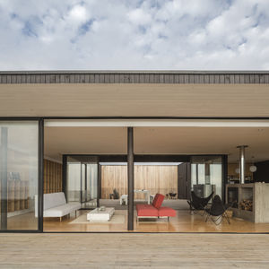 Aluminum lines the glass windows and divides the living spaces from the patio