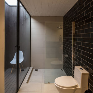 Black Marazzi tiles cover the wall in this Chilean bathroom