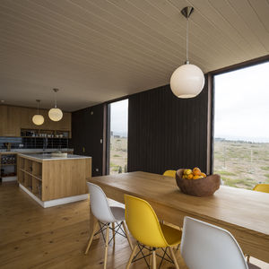 Eames DSW Molded Fiberglass chairs surround the dining table made of local wood