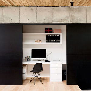 Modern Texas home office with sliding walls, behr black chalkboard paint, concrete walls, and white oak flooring