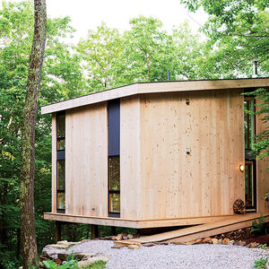 Modern small cantilevered cabin in Massachusetts with knotted pine plank exterior