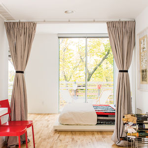 Affordable Kansas City home with west elm bedding and platform bed along with ikea chairs in the bedroom