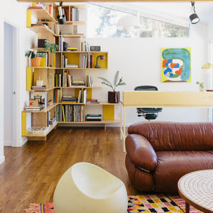 A home office in Portland features colorful built-in bookshelves.