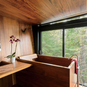 Modern prefab lakeside home in Ontario, Canada with bathroom clad in teak and Bath in Wood tub and sink