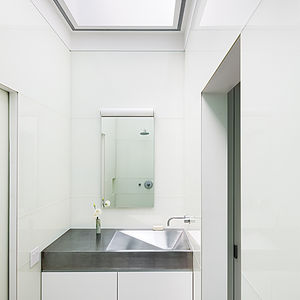 Modern West Village renovation with stainless steel sink, vanity, and painted glass panels in the master bathroom