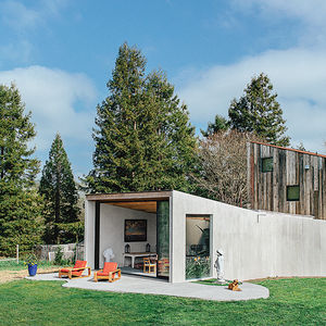 Modern indoor-outdoor concrete dining pavilion facade and barn structure