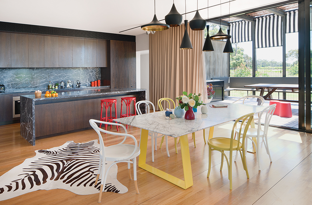 modern lakeside home in Australia kitchen and dining area with tom dixon pendant lamps and steel and marble dining table by chris connell