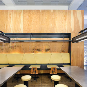 "Chipotle's new design by <a href=""http://www.architectureoutfit.com/"">Architecture Outfit</a> features many contemporary touches like laser cut patterns in its walls and high stools at communal tables."