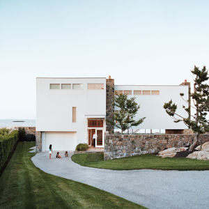 With its flat, white wooden exterior and metal-framed windows that sit flush against the facade, the house exhibits the utilitarian building principles that were so strongly favored by the Bauhaus. It also manages to fuse with the local landscape, using g