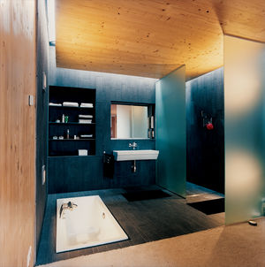 The master bathroom is softly lit by a skylight. The bath, by Laufen, is sunk into the floor to maintain a feeling of space.