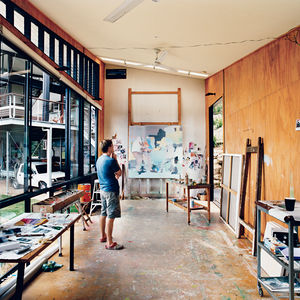 In his detached painting studio, Dunlop considers a work in progress. The building is oriented east-west to avoid direct sunlight, and the long, narrow shape enables the artist to get some distance from his paintings as he works. An oversize front door an