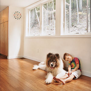 Little boy sitting with pet dog on wooden floor
