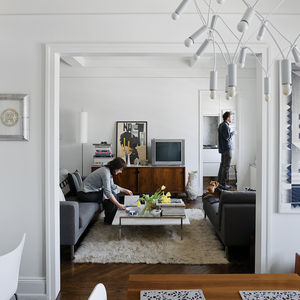 "White lighting elements, finishes, furnishings, walls, and moldings create a feeling of modern openness to this traditional floor plan in New York. Architect Stephan Cassell helped the transplanted couple see past the ""43 layers of paint"" to the modern po"