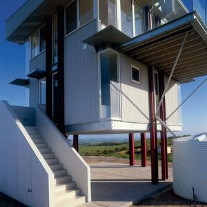 Prefab home on stilts with white staircase