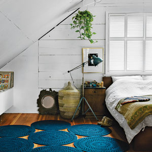 bedroom with white duvet, blue rug, and vintage nightstand